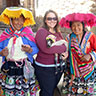 Kim holding a lamb and posing with two Andean women in their traditionl clothing